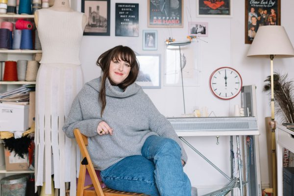 Amber Hards sitting in front of a knitting machine in her studio